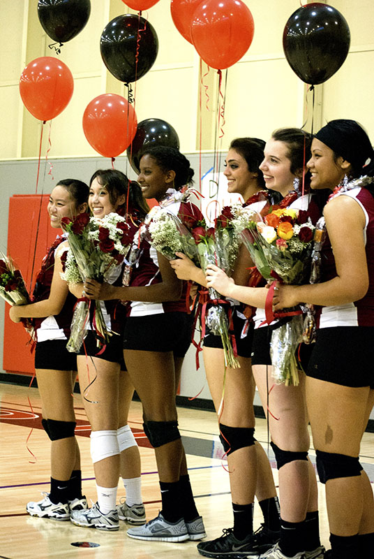 Seniors are congratulated with balloons and a bouquet of flowers before their senior game against Hillsdale High School.